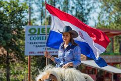 在每年巴拉圭人美国独立日游行期间,一名美丽的妇女骄傲地骑她的与巴拉圭旗子的马 库存图片