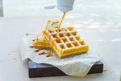 在比利时华夫饼干上把放的焦糖糖浆 免版税图库摄影