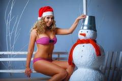 在比基尼泳装和圣诞老人帽子打扮的女孩 免版税库存图片