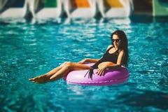 在比基尼泳装的秀丽模型在游泳池 免版税库存照片