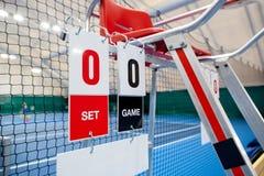 在比赛前审判与记分牌的椅子在网球场 免版税库存图片