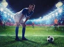 在比赛期间,准备好的足球运动员在体育场踢soccerball 库存图片