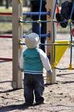 在比赛栅格顶部的小男孩神色 免版税库存图片