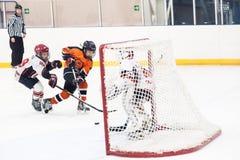 在比赛的攻击在儿童冰曲棍球队之间 免版税库存照片