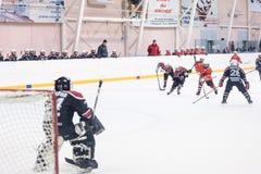 在比赛的攻击在儿童冰曲棍球队之间 免版税图库摄影
