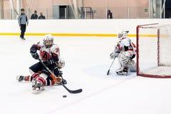 在比赛的攻击在儿童冰曲棍球队之间 图库摄影