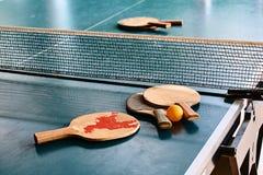 在比赛表上的老乒乓球球拍 图库摄影