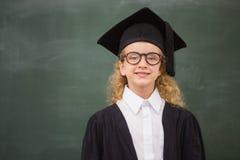 在毕业长袍的逗人喜爱的学生 免版税图库摄影