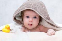 在毛巾下的女婴在浴或阵雨以后的卧室 黄色橡胶说谎在她附近的鸭子和白色洗碗布 纺织品 免版税库存图片