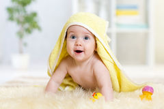 在毛巾下的愉快的婴孩室内在沐浴以后 免版税库存照片