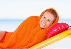 在毛巾包裹的微笑的少妇放置在sunbed 库存照片