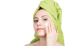 在毛巾打扮的美丽的少妇在面孔做化妆面具 秀丽产业和家庭护肤 免版税库存照片