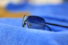 在毛巾的太阳镜 库存照片
