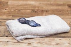 在毛巾的游泳风镜 免版税库存照片