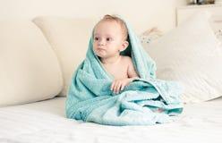 在毛巾盖的小男婴的被定调子的图象坐床 免版税库存图片