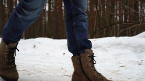 在毛毡起动的走的脚在慢动作的一个冬天风景,冬天步行在森林里 股票视频