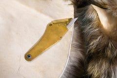 在毛皮兽皮的黄铜刀子 免版税库存照片