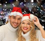 在毛线衣和圣诞老人帮手帽子的Smiiling夫妇 库存图片