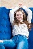 在毛线衣和牛仔裤的愉快的亭亭玉立的模型放松 免版税库存图片