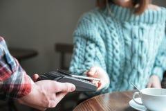 在毛线衣打扮的夫人支付她的与电话的顺序 库存照片