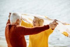 在毛线衣的资深夫妇在海滨 库存图片