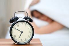 在毯子下的困少妇有她的头的穿上` t要在闹钟特写镜头前面醒 早早醒,没有 免版税库存图片