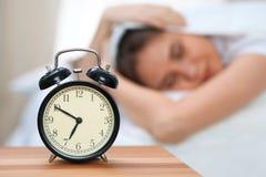 在毯子下的困少妇有她的头的穿上` t要在闹钟特写镜头前面醒 早早醒,没有 免版税库存照片