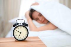 在毯子下的困少妇有她的头的穿上` t要在闹钟特写镜头前面醒 早早醒,没有 库存照片