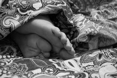 在毯子下的婴孩腿 免版税图库摄影