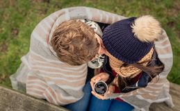 在毯子下的年轻夫妇有亲吻热的饮料的户外 免版税库存图片