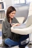 在毯子下的愉快的妇女有膝上型计算机的 库存图片