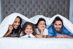 在毯子下的愉快的家庭 库存照片