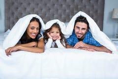 在毯子下的愉快的家庭 免版税库存照片