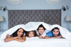 在毯子下的愉快的家庭 免版税库存图片