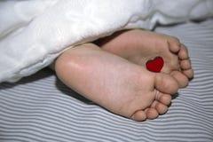 在毯子下的新出生的睡眠,有小心脏的腿为假日 免版税库存图片