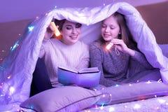 在毯子下的活妈妈和女儿读书有火炬的 库存照片