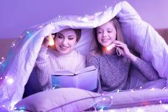 在毯子下的虔诚妈妈和女儿读书 免版税库存照片