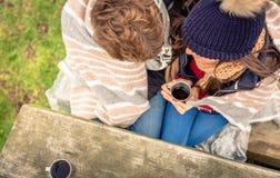 在毯子下的年轻夫妇有热的饮料在a 库存照片
