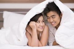 在毯子之下的夫妇 免版税库存图片