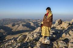 在毯子包裹的一个库尔德人在Mt内姆鲁特火山山顶站立在土耳其在日出 库存照片