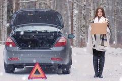 在毯子包裹的女孩被安置在残破的汽车附近 库存照片