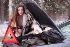 在毯子包裹的女孩被安置在残破的汽车附近 免版税库存图片