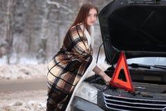 在毯子包裹的女孩被安置在残破的汽车附近 库存图片