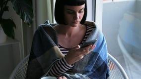在毯子包裹的妇女使用手机4k 股票录像