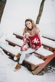 在毯子包裹的少妇喝热的茶在多雪的森林里 免版税库存图片