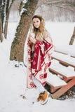 在毯子包裹的少妇喝热的茶在多雪的森林里 免版税库存照片