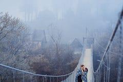 在毯子包裹的迷人的婚礼夫妇在sospension桥梁软软地亲吻在山 秋天山背景 免版税图库摄影