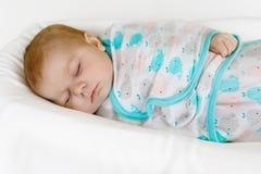 在毯子包裹的逗人喜爱矮小新出生女婴睡觉 免版税库存图片
