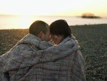 在毯子的夫妇在日落的海滩 免版税库存图片