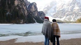 在毯子盖的两年轻女人站立在冻海岸和看山 股票录像
